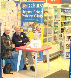 Peter and Elizabeth Davey selling Christmas raffle tickets at Kirkby Stephen co-op