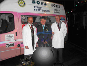 District Governor trussed like the proverbial Christmas turkey with Rotarians Roger and John looking like the cats that got the cream